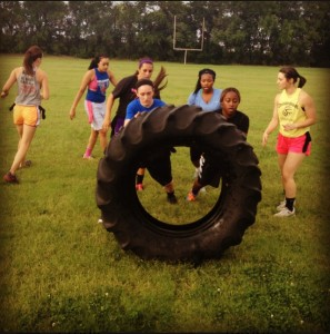 Members of the women's basketball team compete in a tire flipping contest.