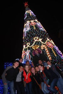 Choir members pose for a picture at the base of a Christmas tree that is next to the Royal Castle.